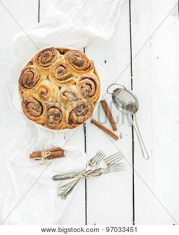 Freshly baked cinnamon buns in dish on a rustic wooden table, top view