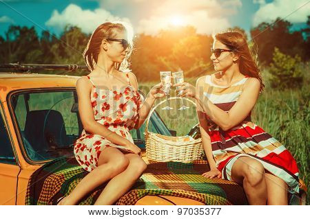 Two Beautiful Women On The Picnic Are Drinking Champagne On The Car.