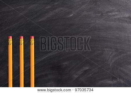 Three new pencils standing in front of a chalkboard with eraser marks. Horizontal format with copy space. Back to School concept.