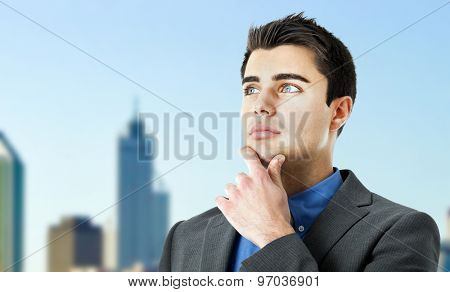 Young man looking forward with city in the background