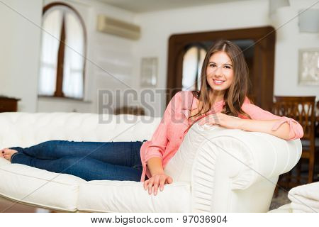Portrait of a smiling young woman relaxing on the couch in her home