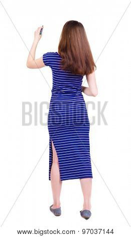 back view of writing beautiful woman. Young girl in dress. Rear view people collection.  backside view of person. Isolated over white background.  Girl in a blue striped dress stands and draws on wall