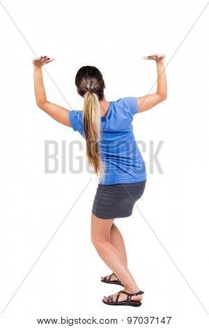 back view of woman  protects hands from what is falling from above.   Isolated over white background. Girl in a gray skirt and blue shirt sitting down holding something heavy overhead.