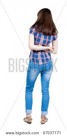back view of standing young beautiful  woman.  girl  watching. Rear view people collection.  A young girl in a checkered blue with red stripes stands with his arms crossed on his back.