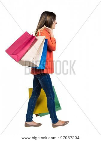 back view of going  woman  with shopping bags . beautiful girl in motion.  backside view of person. Isolated over white background. Girl in a red jacket leaves left laden with heavy shopping bags.