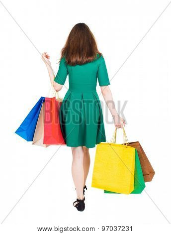 back view of going  woman  with shopping bags . beautiful girl in motion.  backside view of person. Isolated over white background. girl in stylish green dress is holding shopping bags on a bent elbow