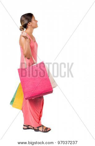 back view of going  woman  with shopping bags . beautiful girl in motion.  backside view of person. Isolated over white background. girl in a red dress is easy with the right paper bags.
