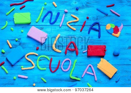 the sentence inizia la scuola, back to school in italian, written with modelling clay of different colors, on a blue rustic wooden background