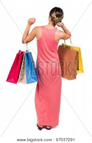 back view of going  woman  in  dress woman with shopping bags . beautiful brunette girl in motion. girl in a light red dress standing holding a set of colored shopping bags and corrects hand hairstyle