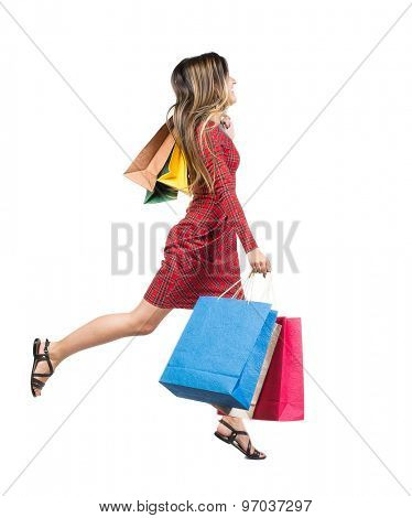 side view woman jumping with shopping bags. beautiful brunette girl in motion.  backside view of person.   Isolated over white background. Long-haired girl in a red plaid dress runs with paper bags