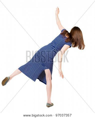 Back view woman Balances waving his arms.   Standing young girl in dress. Rear view people collection. Isolated over white background. Girl in a blue striped dress trying to stay on the right foot.