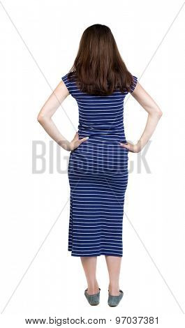 back view of standing young beautiful  woman. girl  watching. Rear view people collection. Isolated over white background. Girl in blue striped dress is putting hands on waist and looking thoughtfully