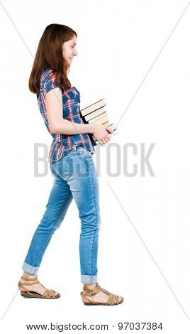 A girl carries a heavy pile of books. side view.  Rear view people collection.   A young girl in a checkered blue with red stripes goes from right to left smiling and carries a stack of books.