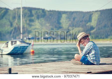 Boy Sitting On Wooden Pier