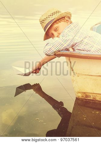 Boy With Paper Ship In Old Boat