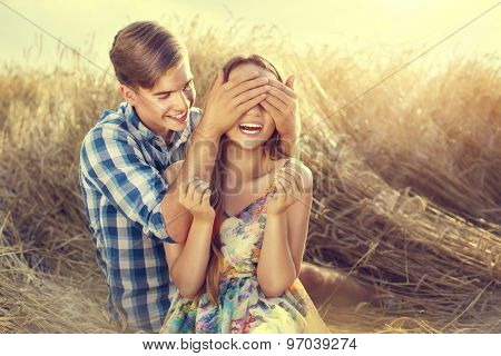 Beauty Couple relaxing on wheat field together. Teenage girlfriend and boyfriend having fun outdoors, kissing and hugging, first love concept. Teenagers Boy and Girl in love together
