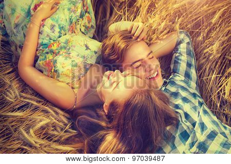 Beauty Couple Lying and relaxing on wheat field together. Teenage girlfriend and boyfriend having fun outdoors, kissing and hugging, first love concept. Teenagers Boy and Girl in love together