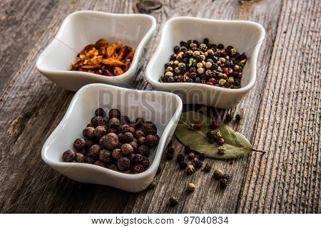different kinds of pepper in white bowls on wooden background