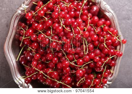 Ripe red currants in metal bowl on table, top view