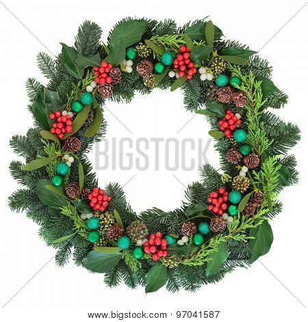 Christmas wreath decoration with green baubles, holly, mistletoe, ivy, pine cones and blue spruce fir over white background.