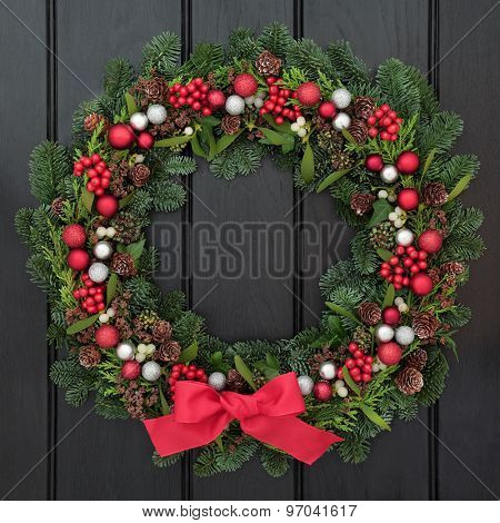 Christmas wreath with red bow and bauble decorations, holly, mistletoe and winter greenery over dark blue oak front door background.
