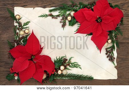 Thanksgiving and christmas poinsettia flower border on parchment paper over old oak background