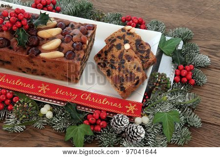 Genoa cake and slices with merry christmas ribbon with holly, mistletoe and winter greenery over oak background.