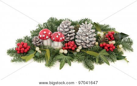 Christmas decoration with fly agaric mushroom bauble, holly, mistletoe, ivy, pine cones and traditional winter greenery over white background.