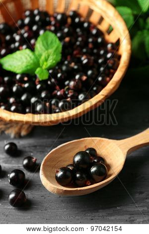Ripe black currant on wooden background