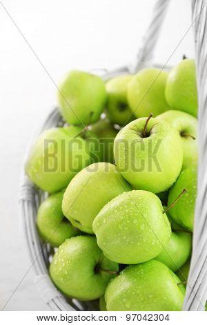 Green apples in wicker basket, closeup