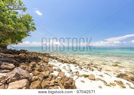 White sand beach and tropical sea with rocky coast