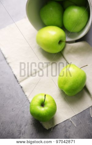 Green apples on wooden table with napkin, closeup
