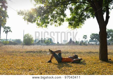 A tourist relax near the root of tree near temples in Bagan