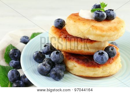 Fritters of cottage cheese with blueberries in plate, closeup