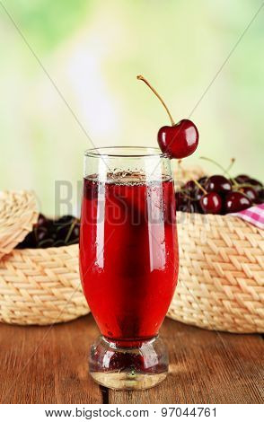 Glass of cherry juice on wooden table on light blurred background
