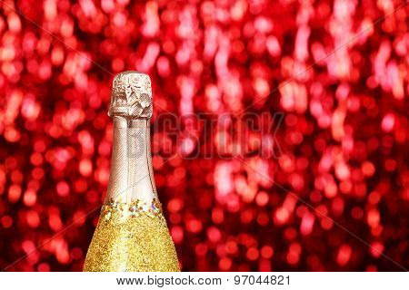 Decorated champagne bottle on bright sparkling blurred background