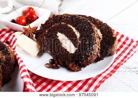 Delicious chocolate roll in white saucer on checkered napkin, closeup