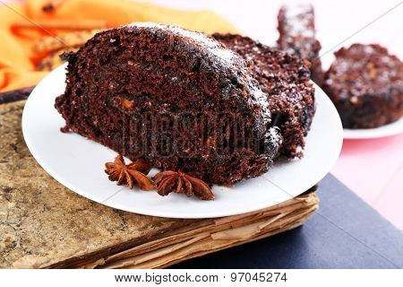 Delicious chocolate roll in saucer on book, closeup