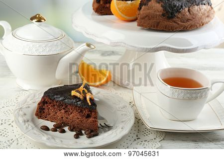 Cake with Chocolate Glaze and orange on plate, on wooden table, on light background