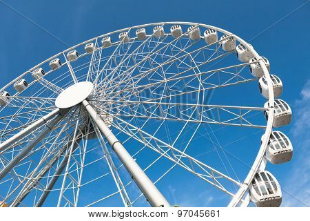 modern white ferris wheel against blue sky background