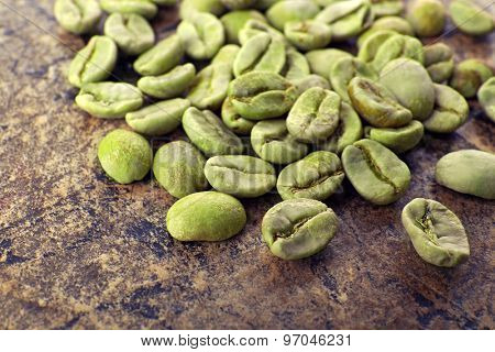 Heap of green coffee beans on table close up