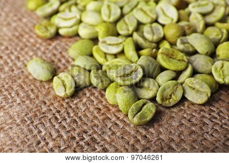 Heap of green coffee beans on sackcloth close up