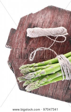 Fresh asparagus on cutting board isolated on white