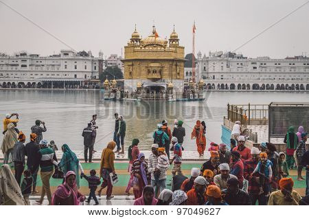 AMRITSAR, INDIA - 01 MARCH 2015: Pilgrims at the Golden Temple, the holiest Sikh gurdwara in the world. Post-processed with texture and grain.