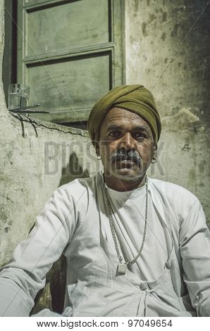 GODWAR REGION, INDIA - 12 FEBRUARY 2015: Indian man dressed in traditional clothes sits on kitchen floor next to window. Post-processed with grain, texture and colour effect.