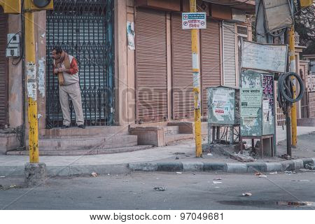 JODHPUR, INDIA - 12 FEBRUARY 2015: Man stands on doorway of building in empty street and looks around the corner. Post-processed with grain, texture and colour effect.