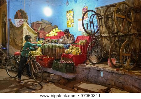 JODHPUR, INDIA - 07 FEBRUARY 2015: Grocery store next to wooden trolleys on big wheels used for transport of goods with store owner and young boy on bicycle.