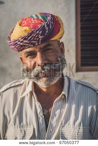 GODWAR REGION, INDIA - 14 FEBRUARY 2015: Adult Indian man with colorful turban and curled mustache sits in street. Post-processed with grain, texture and colour effect.