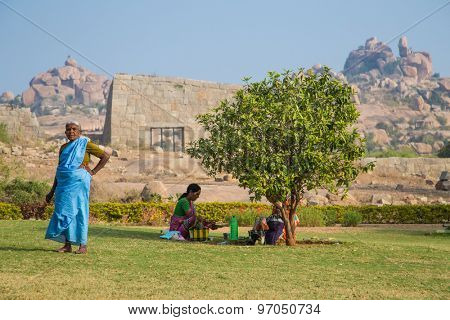 HAMPI, INDIA - 30 JANUARY 2015: Elderly woman stands on small grass field next to tree and family.