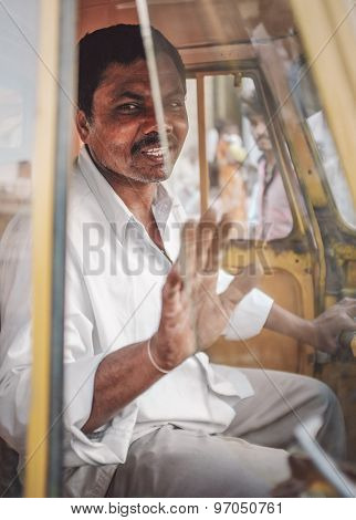 KAMALAPURAM, INDIA - 02 FABRUARY 2015: Indian delivery man gesticulats while passing by in a three-wheeler. Post-processed with grain, texture and colour effect.